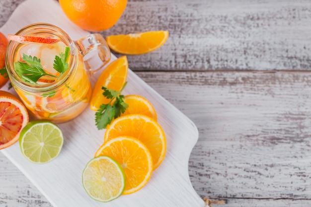 Acqua di agrumi ed erbe per la disintossicazione o la dieta in bottiglie di vetro su tavola di legno