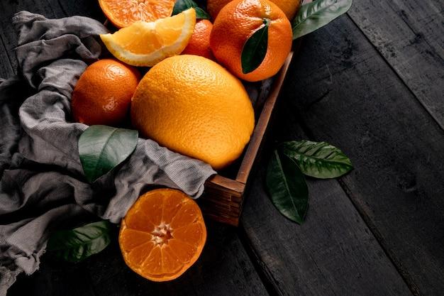 Agrumi - arance e mandarini in una scatola di legno si chiudono. foto di alta qualità