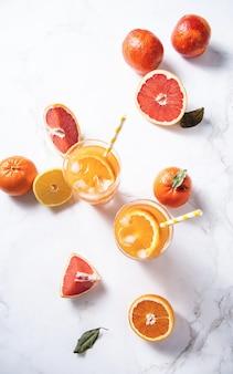 Succo di agrumi in due bicchieri e frutta fresca mandarino arancia pompelmo e limone su uno sfondo di marmo vista dall'alto e distesi