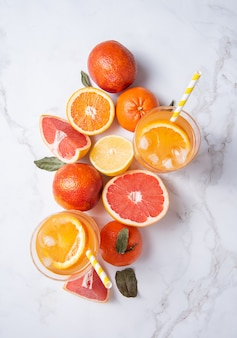 Succo di agrumi in due bicchieri e frutta fresca mandarino, arancia, pompelmo e limone su fondo marmorizzato