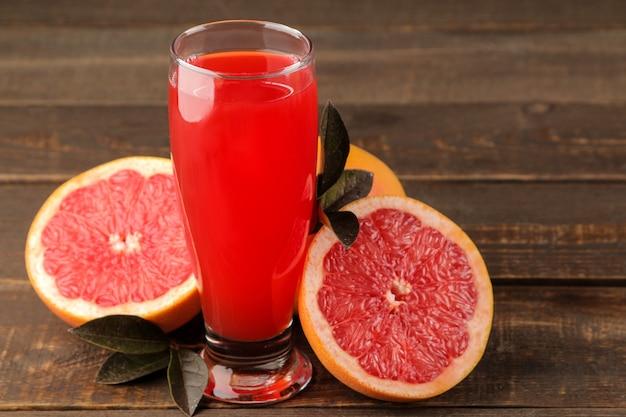 Succhi di agrumi. succo di pompelmo in un bicchiere con frutta fresca su un tavolo di legno marrone