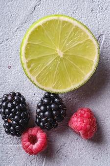 Fetta di agrumi, lampone e bacche di mora, frutti estivi sani sul tavolo in cemento di pietra, macro vista dall'alto