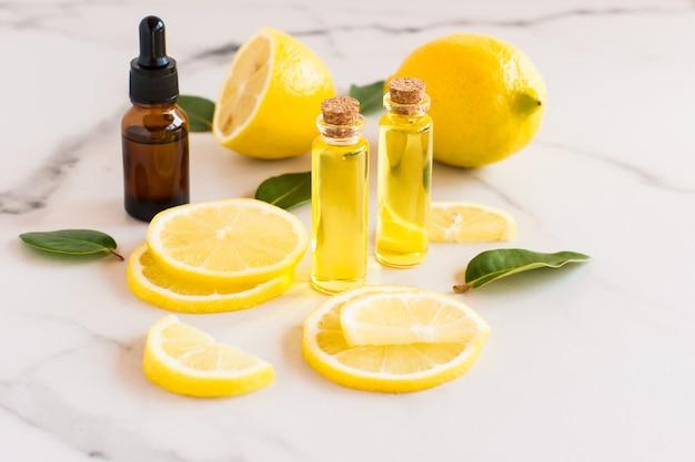 Olio di agrumi, limone naturale, vitamina c in bottiglie di vetro su fondo marmoreo. medicina alternativa.