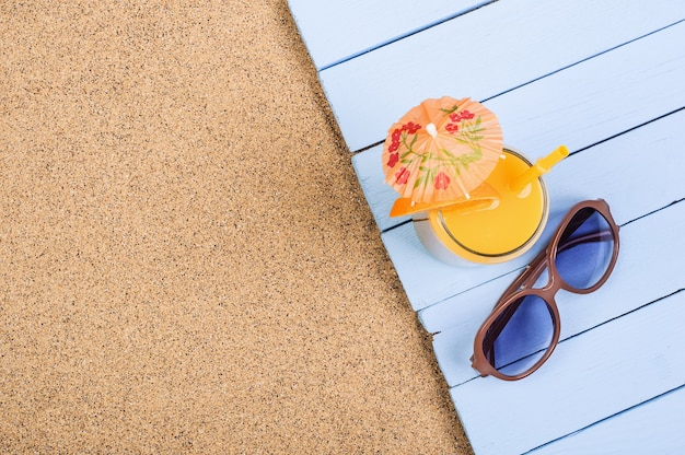 Succo d'arancia di agrumi in un bicchiere e occhiali da sole su tavole blu sulla spiaggia