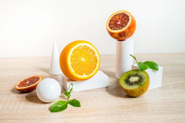 Concetto di natura morta di agrumi con limone lime e arancia su supporti e podi bianchi