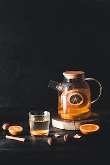 Tè agli agrumi in una teiera trasparente su uno sfondo di cemento scuro. bevanda salutare, vegana, prodotto ecologico.