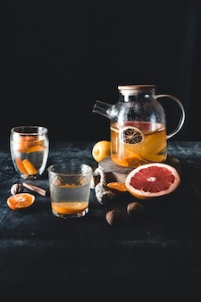 Tè agli agrumi in una teiera trasparente su un muro di cemento scuro. bevanda salutare, vegana, prodotto ecologico.