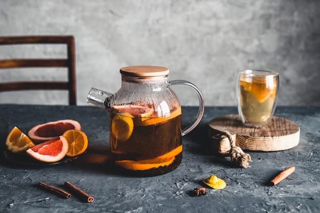 Tè agli agrumi in una teiera trasparente su uno sfondo grigio cemento. bevanda salutare, vegana, prodotto ecologico.