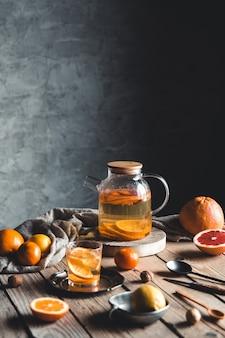 Tè agli agrumi in una teiera trasparente su un tavolo con pompelmo e su un tavolo di legno. bevanda salutare.