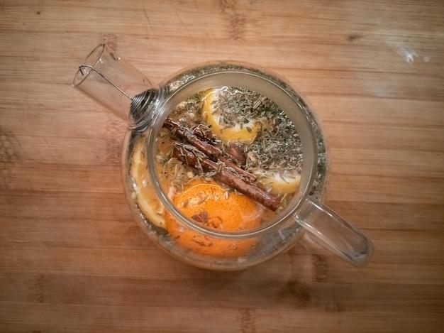 Tè agli agrumi con cannella in una teiera di vetro vista dall'alto