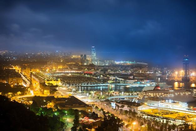Città di barcellona di notte. vista sul porto e sul paesaggio urbano con cielo blu scuro