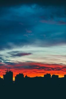 Silhiouettes di edifici della città su sfondo vivido del cielo al tramonto multicolore