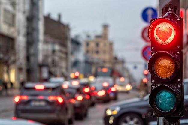 Una città che attraversa con un semaforo, semaforo a forma di cuore rosso nel semaforo, concetto di san valentino