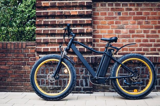 Bicicletta elettrica della città vicino ad un muro di mattoni. trasporto urbano ecologico