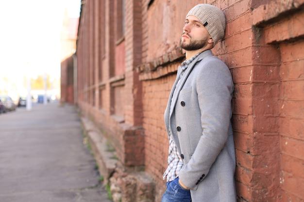 Vita di città. giovane alla moda in cappotto grigio e cappello in piedi per strada in città.