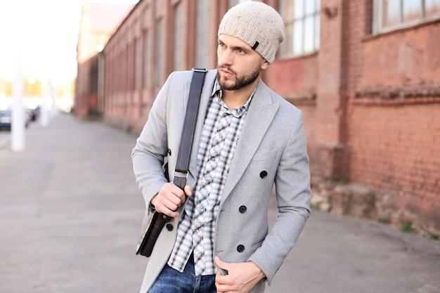 Vita di città. giovane alla moda in cappotto grigio e cappello che cammina per strada in città.