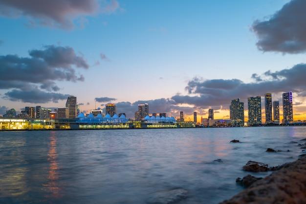 Città di miami florida, panorama al tramonto con edifici commerciali e residenziali e ponte sulla baia di biscayne. vista notturna dell'orizzonte.