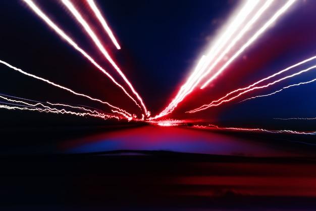 Prospettiva delle luci notturne della città sfocata dall'alta velocità dell'auto.