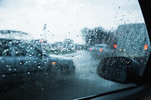 Strada di città attraverso le automobili del parabrezza sfondo astratto goccia d'acqua sulle luci di vetro e pioggia.