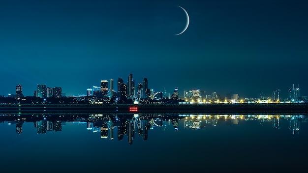 Paesaggio urbano di notte con la luna e lo skyline della città sullo sfondo