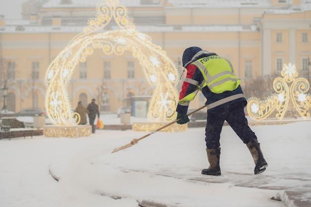 Il ragazzo del servizio urbano pulisce la neve dalle strade con la pala b