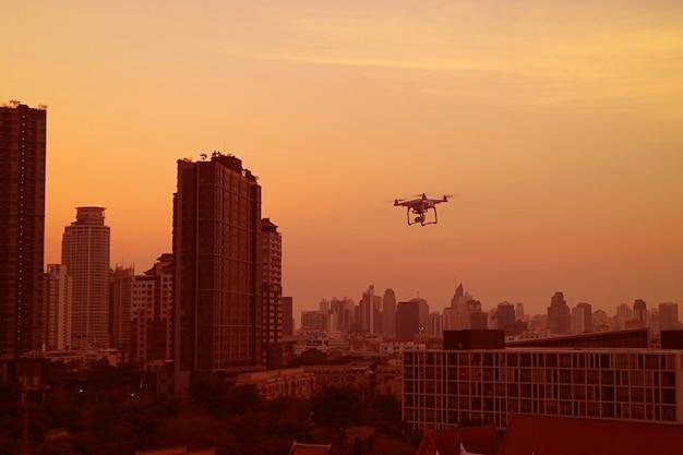 Città al tramonto con un drone che frigge nel cielo arancione dorato