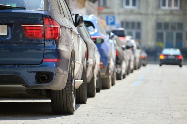Traffico cittadino con auto parcheggiate in fila sul lato strada.