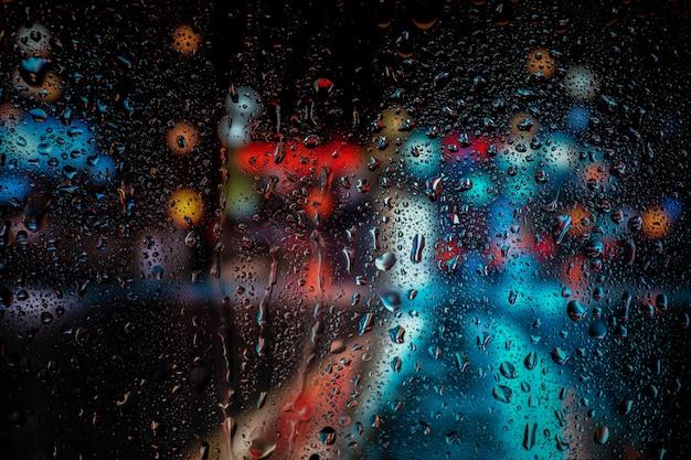 Vista della città attraverso una finestra in una notte piovosa con bokeh luce stradale.