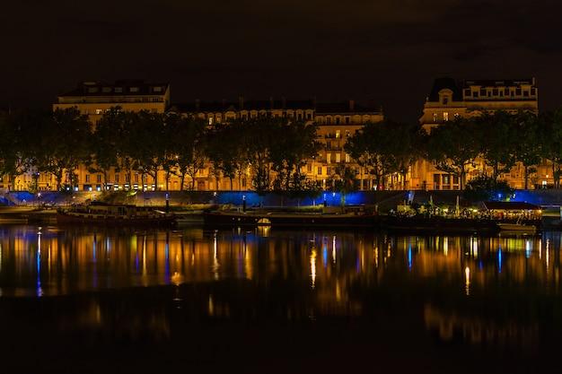 Paesaggio urbano di lione francia con riflessi nell'acqua durante la notte