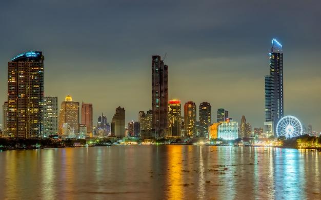 Paesaggio urbano di costruzione moderna vicino al fiume nella notte. edificio per uffici di architettura moderna. grattacielo con cielo serale. fotografia notturna dell'edificio sul lungofiume. condominio luce aperta nella notte.