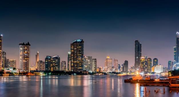 Paesaggio urbano di costruzione moderna vicino al fiume nella notte. edificio per uffici di architettura moderna. grattacielo con cielo serale. fotografia notturna dell'edificio sul lungofiume.