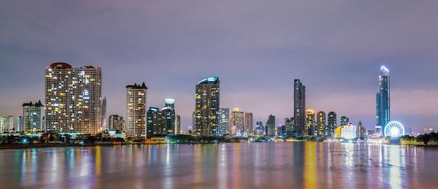 Paesaggio urbano di costruzione moderna vicino al fiume nella notte. edificio per uffici di architettura moderna. grattacielo con cielo serale.
