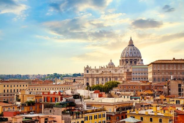 Vista del paesaggio urbano di roma al tramonto con la cattedrale di san pietro in vaticano.