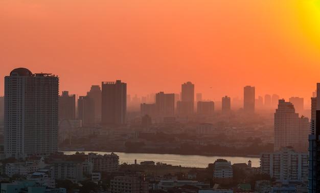 Paesaggio urbano con aria inquinata e luce del tramonto