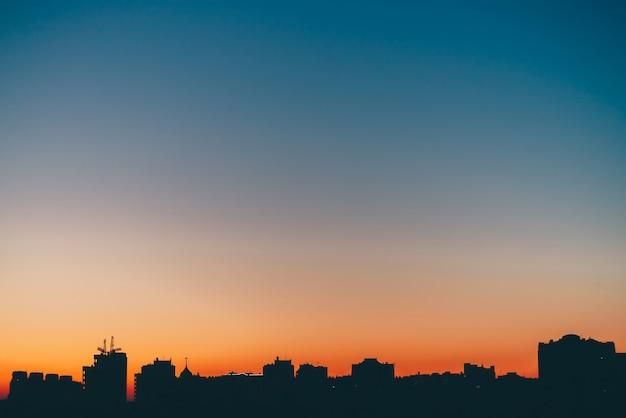 Paesaggio urbano con meravigliosa alba vivida varicolored. cielo blu stupefacente con luce solare arancio sopra le siluette scure delle costruzioni della città. sfondo suggestivo di calda alba. copia spazio.
