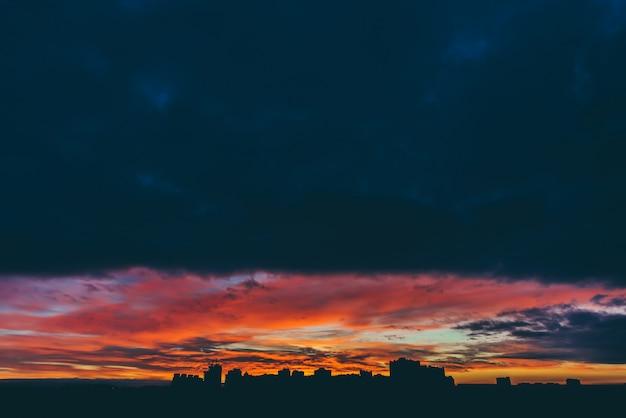 Paesaggio urbano con meravigliosa alba vivida varicolored. cielo nuvoloso multicolore drammatico stupefacente sopra le siluette scure delle costruzioni della città. sfondo atmosferico di alba in tempo nuvoloso. copia spazio.