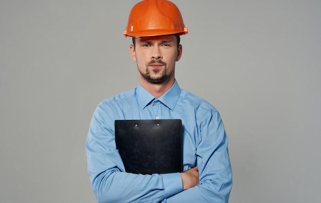 Uomo di architettura dell'ingegnere civile in casco arancione