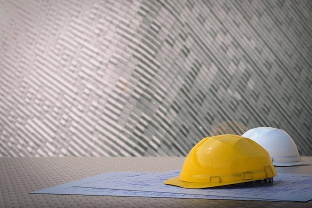 Concetto di ingegnere civile con caschi di sicurezza e carta cianografica