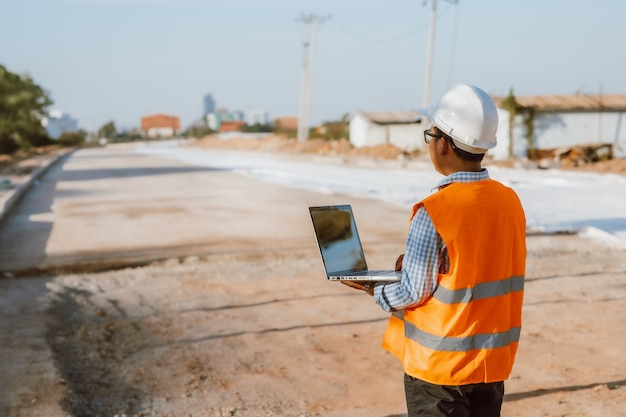 Ingegnere civile in cantiere utilizzando computer portatile controllando il lavoro. gestione in cantiere.