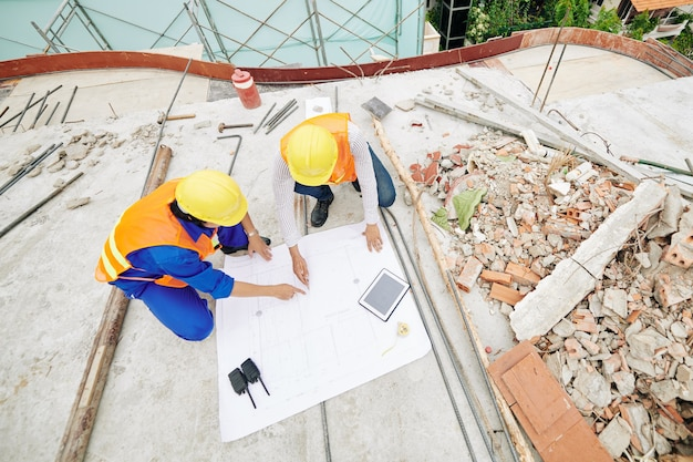 Ingegneri civili indicando il piano di costruzione e discutendo i dettagli, vista dall'alto