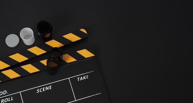 Ciak e rotolo di pellicola su sfondo nero. utilizza nel settore della produzione di film e video.