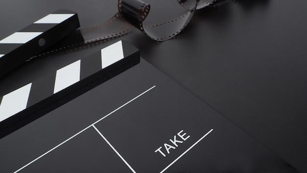 Batacchio o ardesia di film e rullino su sfondo nero.