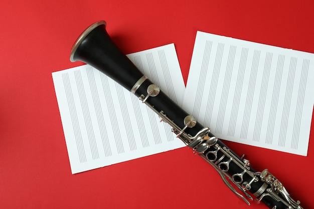 Clarinetto e fogli di musica su sfondo rosso.