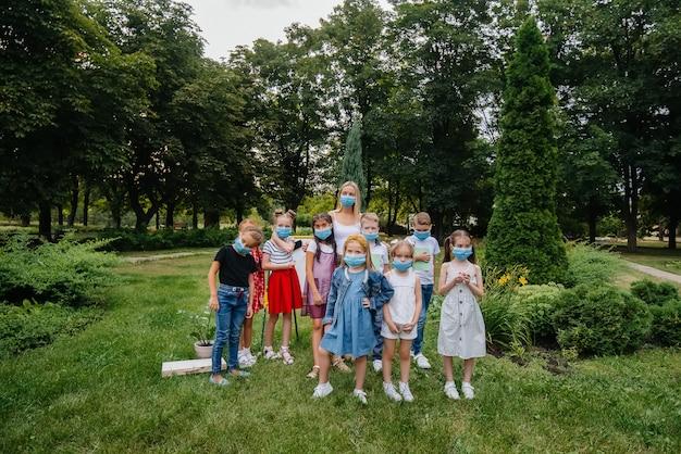 Una classe di scolari mascherati è impegnata in allenamenti all'aperto durante l'epidemia. ritorno a scuola, apprendimento durante la pandemia.