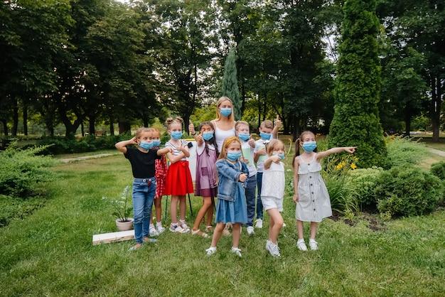 Una classe di scolari mascherati è impegnata in allenamenti all'aperto durante l'epidemia