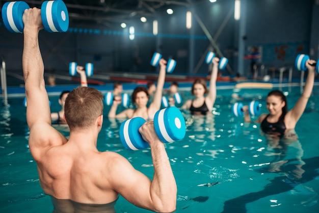 Classe con istruttore in allenamento con manubri aqua