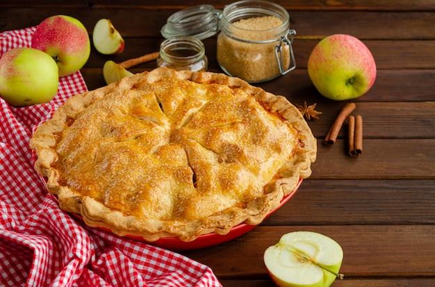 Torta di mele americana classica con cannella su uno sfondo di legno scuro.