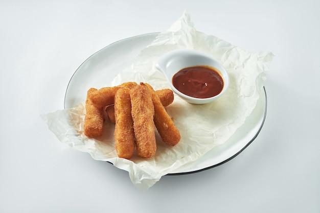 Uno spuntino classico alla birra è costituito da bastoncini di mozzarella fritti in un piatto bianco. sfondo bianco Foto Premium
