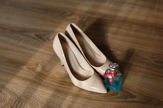 Le scarpe classiche del tacco alto delle donne beige si chiudono su sul pavimento di legno. set matrimonio moda - scarpe da sposa e profumi. dettagli nuziali