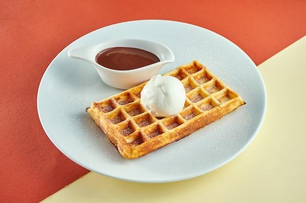 Cialde belghe classiche con gelato e salsa dolce in un piatto bianco su superficie colorata.